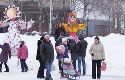 Russian holiday Maslenitsa. People walking and taking the photos near Shrovetide doll during the holiday Shrovetide Pancake Week, russian name is Maslenitsa Royalty Free Stock Photos