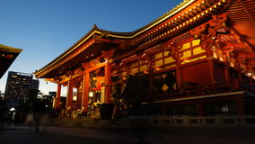 People are walking in to the red Temple of Sensoji shrine. stock footage