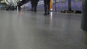 People walking in train station with baggage. Luggage going on travel or business trip. Mostly out of focus and blurry. Transport concept with feet and and legs stock video
