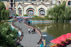 People walking on twisty bridge in the amusement park. View from top on the big area Stock Photos