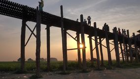 People walking on the Ubein bridge in Mandalay, Myanmar. People walking on the Ubein bridge at sunset in Mandalay, Myanmar. Ubein Bridge across the Taungthaman stock video footage