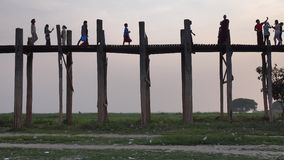 People walking on the Ubein bridge in Mandalay, Myanmar. People walking on the Ubein bridge at sunset in Mandalay, Myanmar. U Bein Bridge is a crossing that stock video