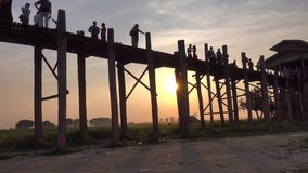 People walking on the Ubein bridge in Mandalay, Myanmar. People walking on the Ubein bridge at sunset in Mandalay, Myanmar. The unique Ubein Bridge, within the stock video footage