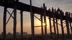 People walking on the Ubein bridge in Mandalay, Myanmar. U Bein Bridge is a crossing that spans the Taungthaman Lake near Amarapura in Myanmar stock footage
