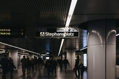 People walking under the directional sign inside Stephansplatz station in Vienna, Austria. Vienna, Austria - November 25, 2018: People walking under the stock photography