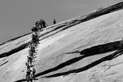 People walking up Half Dome. Black and white view of line of people walking up side of Half Dome rock in Yosemite National Park, California, U.S.A Royalty Free Stock Image