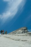 People walking up Half Dome. Rear view of people walking up Half Dome rock formation in Yosemite National Park, California, U.S.A Stock Photos