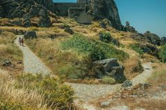 People walking up a path covered by bushes near Monsanto. People walking up stone path towards castle on top of rocky hill covered by pretty flowers and dry stock photo
