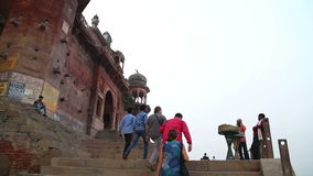 People walking up the stairs towards a building in Varanasi. stock video