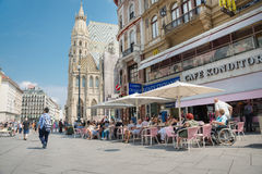 People walking  in Vienna. VIENNA, AUSTRIA - AUGUST 3, 2015: people sitting and walking at cafe  in the historic Stephansplatz center of Vienna on august 3, 2015 Royalty Free Stock Image