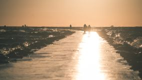 People walking on the wavebreaker in the sea - vintage effect. People walking on the  wavebreaker in the sea with waves crushing over in sunset - vintage effect Stock Image