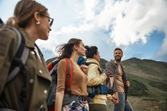 Active people enjoying their journey and smiling. People walking. Young active travelers walking in the mountains and enjoying their journey stock image