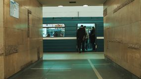 People walks into metro train at empty station, man with skateboard. People walks into underground metro train at empty station, man with skateboard. Slowmotion stock video footage