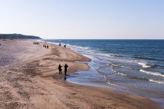 People that walks on the seashore in autumn stock image