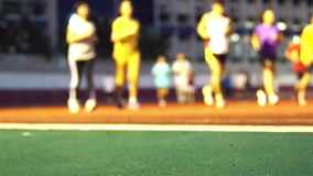 People warm up onto running track in blurry for background stock footage