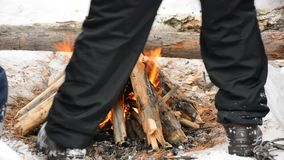People are warming around the fire in the winter forest.  stock footage