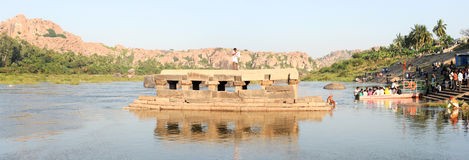People washing clothes and crossing the river by boat at Hampi Royalty Free Stock Photo