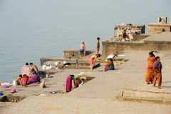 People washing clothes on sacred river Narmada ghats at Maheshwa Stock Images