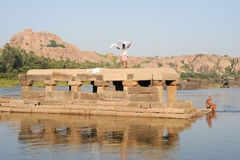 People washing clothes and themselves in the river at Hampi Stock Photography
