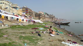 People washing and drying laundry on string on shore of Ganges. VARANASI, INDIA - 20 FEBRUARY 2015: People washing and drying laundry on string on shore of stock video footage