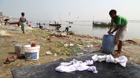 People washing laundry on shore of Ganges, while boats sail through river. VARANASI, INDIA - 20 FEBRUARY 2015: People washing laundry on shore of Ganges, while stock footage