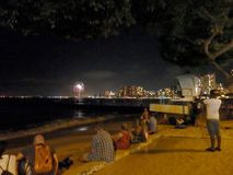 People watch Fireworks Show on Queens Beach royalty free stock photography