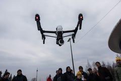 People watch the flight of Dji Inspire 1 drone UAV. Saint-Petersburg, Russia - 26 MARCH 2016; People watch the flight of Dji Inspire 1 drone UAV quadcopter which royalty free stock photo