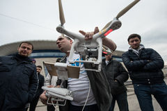 People watch the flight of Dji Inspire 1 drone UAV. Saint-Petersburg, Russia - 26 MARCH 2016; People watch the flight of Dji Inspire 1 drone UAV quadcopter which royalty free stock photography