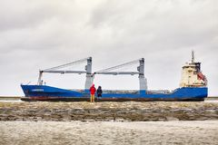 People watch Langeoog cargo ship leaving the port of Swinoujscie. Swinoujscie, Poland - January 28, 2018: People watch Langeoog cargo ship leaving the port of Stock Image