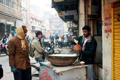 People watch to the seller of street food at the cold morning Royalty Free Stock Photography