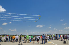 Airplanes formation. People looking at stunt aircraft flying in formation at the Bucharest Air Show on June 22, 2014 in Bucharest, Romania Stock Images