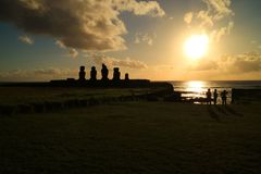 People watching beautiful sunset over the Pacific ocean at Ahu Tahai with Moai statues, Easter Island of Chile stock photo