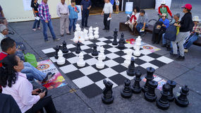 People watching a big chess game in the street Stock Image