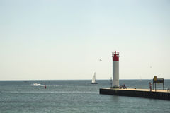 People watching boats at lighthouse Royalty Free Stock Image
