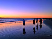 People watching a colorful sunset along beach shoreline Stock Photos