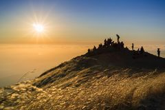 People watching a colorful sunset over a sea of clouds royalty free stock photography