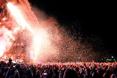 People watching a concert by the famous band Arcade Fire, while throwing confetti from the stage Stock Photos