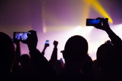 People watching a concert and someone shooting photo and video with a cellphone stock image