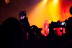 People watching a concert and someone shooting photo and video with a cellphone royalty free stock photography