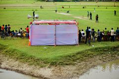 People watching cricket games around a village ground. Bangladeshi people gathered together to watch a cricket game in the village ground unique editorial photo royalty free stock photography