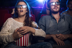 People watching a 3d movie at the cinema. Young teenagers at the cinema wearing glasses and watching a 3d movie, a girl is eating popcorn, entertainment and Royalty Free Stock Photo