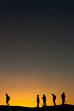 People watching a desert sunset. A group of people in silhouette against an orange desert sunset royalty free stock photography