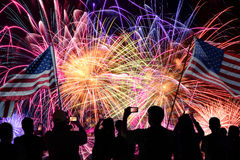 People Watching Fireworks Display with Flags. Group of people watching fireworks on 4th of July and using cellphones royalty free stock image
