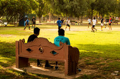 People watching kids playing football in Gurgaon. Gurgaon, India ; 23rd May 2015: Spectators watching a informal game of football between some people in Gurgaon Stock Photos
