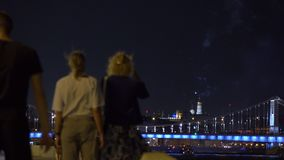People watching and making photoes of fireworks over bridge. 4K video stock video
