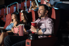 People watching a movie and eating popcorn. Crowd of good looking people eating snacks and having a good time at the movie theater Stock Photography
