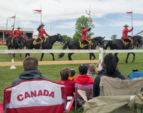 People watching RCMP Musical Ride. Some people sitting on Canada chair and watching the RCMP musical ride in Chesterville, Ontario, CAnada Royalty Free Stock Photo