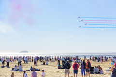 People are watching the Red Arrows flying. Weston-super-Mare, United Kingdom -  June 17, 2017: A large crowd of people at the beach are watching the Red Arrows Stock Photos