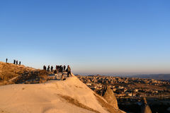 People watching sunrise with balloons on cliff in Goreme. Cappadocia. Turkey. Goreme, Turkey - October 15, 2016: People watching sunrise with balloons on cliff Royalty Free Stock Photography