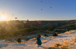 People watching sunrise with balloons on cliff in Goreme. Cappadocia. Turkey. Goreme, Turkey - October 15, 2016: People watching sunrise with balloons on cliff Stock Photos